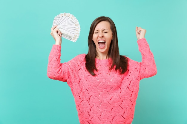 Gekke jonge vrouw in roze trui schreeuwen, met veel bos dollars bankbiljetten, contant geld, gebalde vuist als winnaar geïsoleerd op blauwe achtergrond. mensen levensstijl concept. bespotten kopie ruimte.