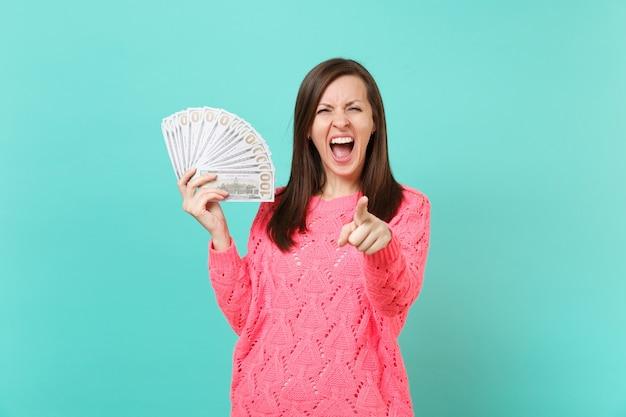 Gekke jonge vrouw in roze trui schreeuwen, wijzende wijsvinger op camera houden veel stelletje dollars bankbiljetten, contant geld geïsoleerd op blauwe achtergrond. mensen levensstijl concept. bespotten kopie ruimte.