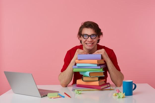 Gekke jongeman met bril, in rood t-shirt, man zit aan tafel en werkt met laptop en boeken, leunde op een stapel boeken, ziet er slecht uit. geïsoleerd op roze achtergrond.