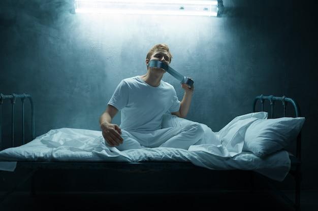 Gekke man plakte zijn mond dicht, slapeloosheid, donkere rokerige kamer. psychedelische persoon die elke nacht problemen heeft, depressie en stress, verdriet, psychiatrisch ziekenhuis
