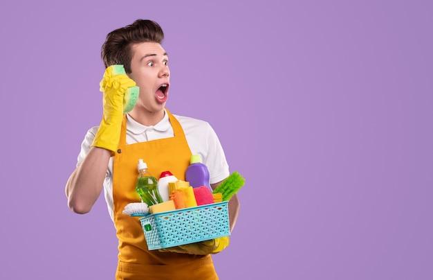 Gekke mannelijke huishoudster met container van verschillende wasmiddelen houden spons in de buurt van oor als telefoon en wegkijken in verbazing tegen violette achtergrond