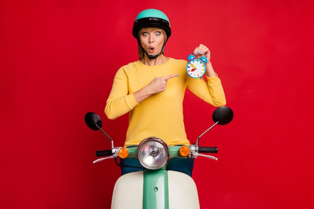 Gekke meisje bromfiets bestuurder houdt klok wijsvinger op rode muur