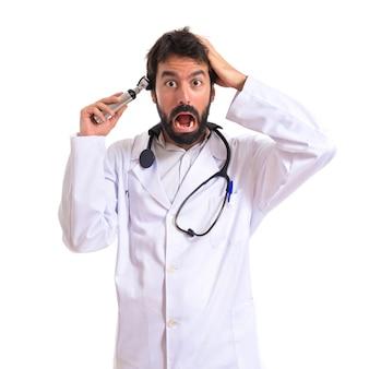 Gekke otorhinolaryngologist met zijn otoscoop over witte achtergrond