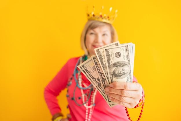 Gekke senior vrouw met aanhouden van geld cashback in stijlvolle kleding financiën concept