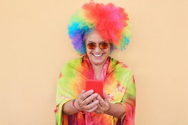 Gekke senior vrouw met behulp van mobiele telefoon-app