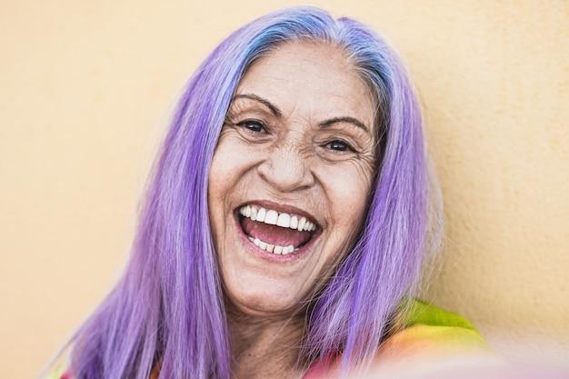 Gekke senior vrouw met paarse haren die een selfie nemen - gelukkige bejaarde