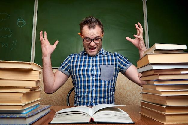 Gekke slordige vermoeide ongeschoren jonge man in glazen die een boek lezen bij de lijst met stapels boeken tegen de achtergrond van het bord.