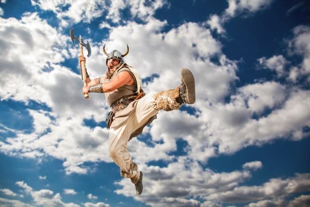 Gekke sterke viking met traditionele klederdracht die vanuit de lucht aanvalt en met boze ogen naar de camera kijkt