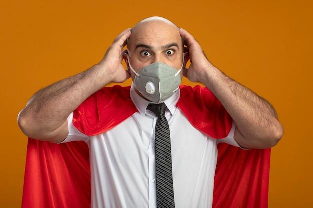 Gekke superheld zakenman in beschermend gezichtsmasker en rode cape met gekke verbaasde blik van verrassing hand in hand op zijn hoofd