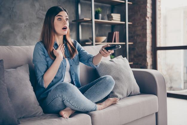 Gekke verbaasde sprakeloze dame houd afstandsbediening vast kijk televisie