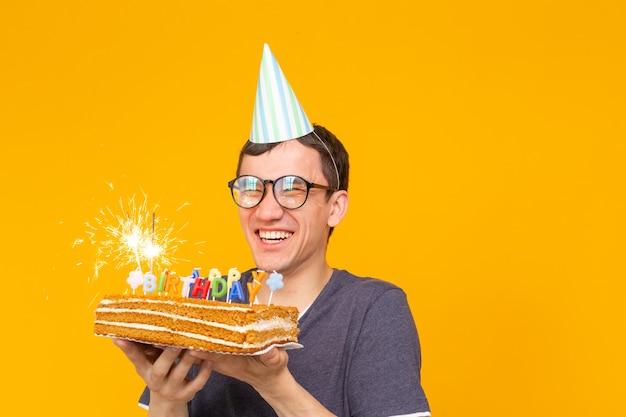 Gekke vrolijke aziatische man met een bril met brandende kaars in zijn handen en felicitatie zelfgemaakte cake op een gele achtergrond met kopieerruimte. verjaardag en jubileumfeest