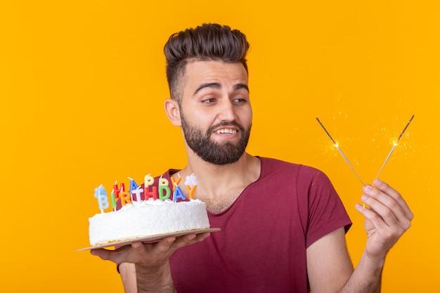 Gekke vrolijke jonge kerel met een brandende kaars in zijn handen en een felicitatie zelfgemaakte cake op een gele achtergrond. verjaardag en jubileum viering concept.