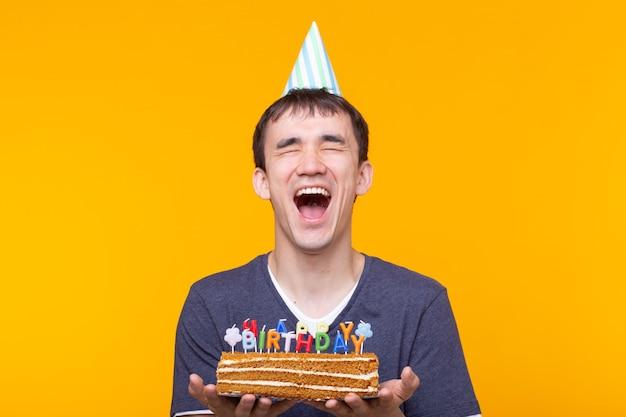 Gekke vrolijke jonge man in glazen en papier felicitatie hoed met cake