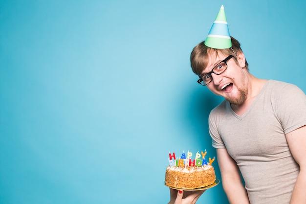 Gekke vrolijke jongeman in glazen en papier felicitatie hoeden met taarten gelukkige verjaardag staande op een blauwe muur. jubileum gefeliciteerd concept. promo ruimte