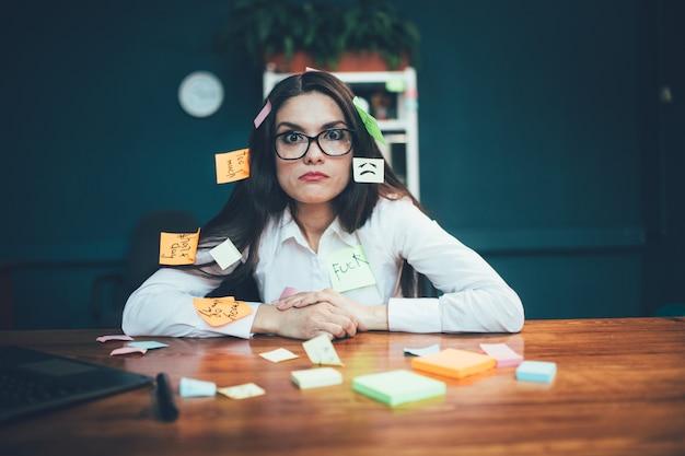 Gekke vrouw die met herinneringsetiketten bij bureau zitten