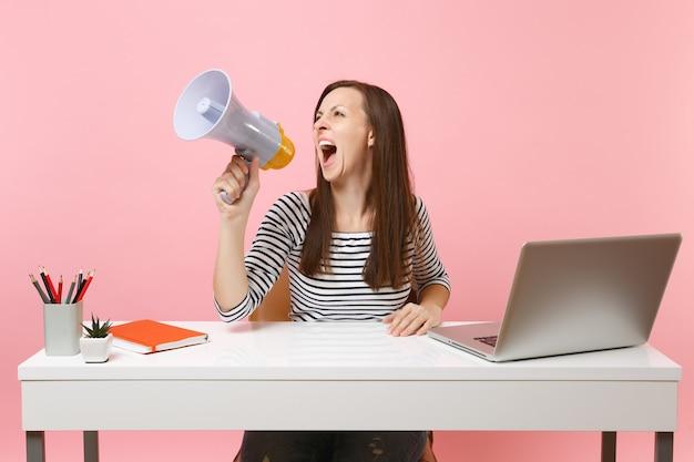 Gekke vrouw in casual kleding schreeuwend in megafoon terwijl ze zitten, werk aan een wit bureau met pc-laptop geïsoleerd op pastelroze achtergrond. prestatie zakelijke carrière concept. kopieer ruimte voor advertentie.