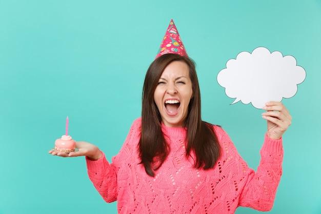 Gekke vrouw in verjaardagshoed schreeuwen, met taart met kaars, lege blanco say cloud, tekstballon voor promotionele inhoud geïsoleerd op blauwe achtergrond. mensen levensstijl concept. bespotten kopie ruimte.