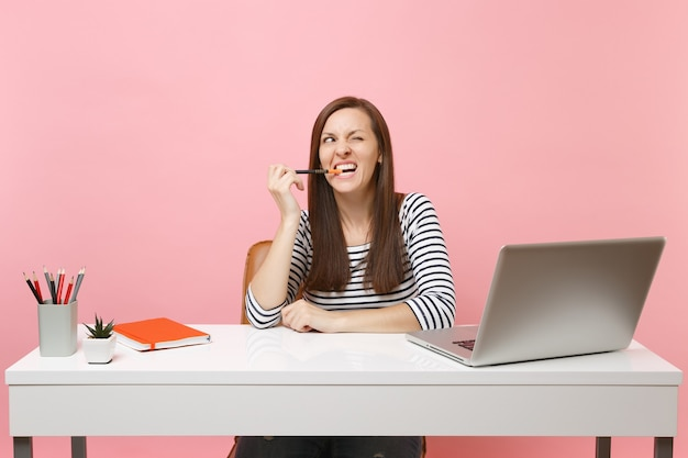 Gekke vrouw in vrijetijdskleding knaagt aan potlood en kijkt knipperend naar het werk aan een wit bureau met een moderne pc-laptop