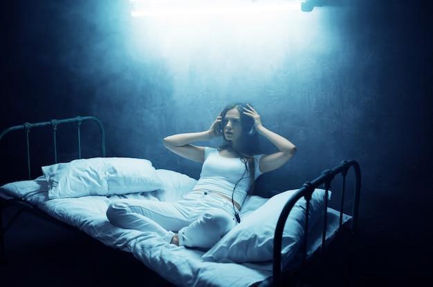 Gekke vrouw luistert naar muziek in bed, donkere kamer ... psychedelische vrouwelijke persoon die elke nacht problemen heeft, depressie en stress, verdriet, psychiatrisch ziekenhuis