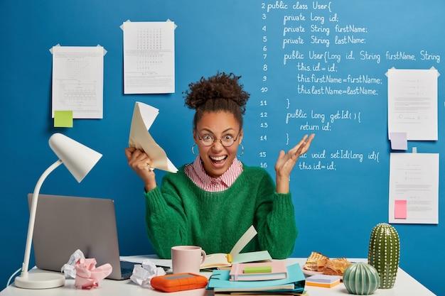 Gekke vrouwelijke ondernemer wordt gek van veel werk, schreeuwt boos, houdt verfrommeld papier vast, benadrukt dat ze een deadline heeft