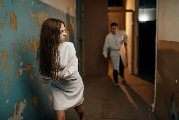 Gekke vrouwelijke patiënt in dwangbuis loopt weg van de psychiater, psychiatrisch ziekenhuis.