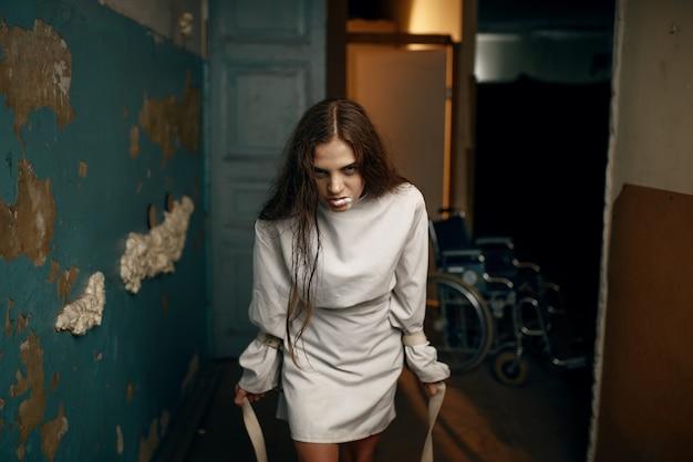 Gekke vrouwelijke patiënt in keurslijf in een vlaag van woede, psychiatrisch ziekenhuis.
