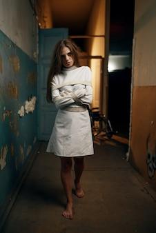 Gekke vrouwelijke patiënt in keurslijf, psychiatrisch ziekenhuis. vrouw in dwangbuis die behandeling ondergaat in kliniek voor geesteszieken