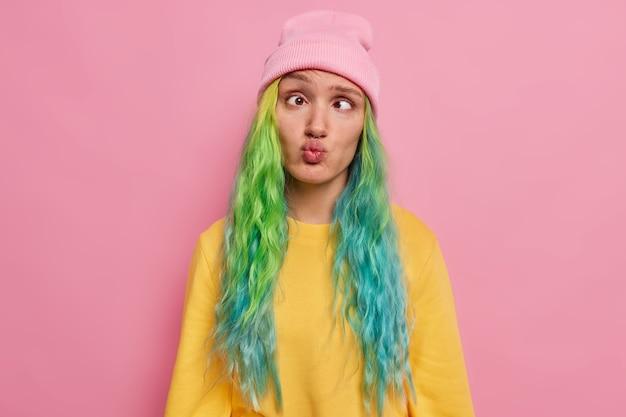Gekke vrouwelijke student met gekleurd haar heeft plezier alleen ongemakkelijke uitdrukking dwaast rond na een hele dag studeren kruisen ogen pruilende lippen draagt hoed en jumper poses op roze studio