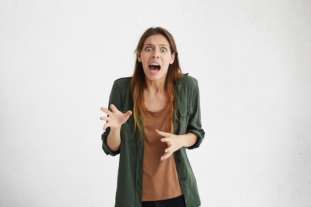Gekke wanhopige vrouw die geschokt kijkt met wijd geopende mond en afgeluisterde ogen schreeuwend van afgrijzen.
