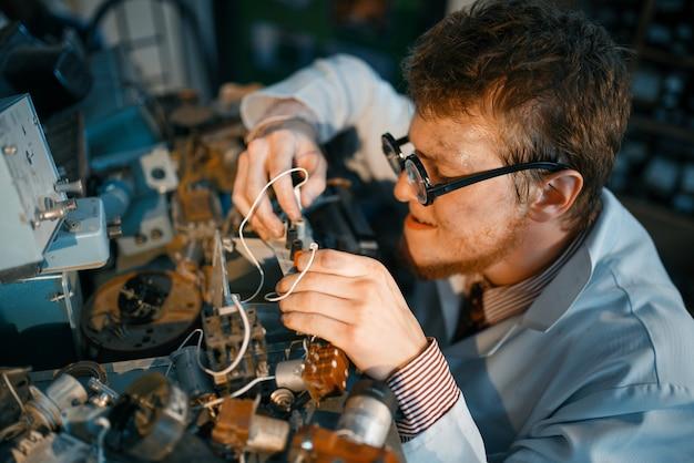 Gekke wetenschapper prototyping elektrisch apparaat in laboratorium.