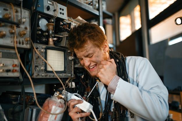Gekke wetenschapper werkt met elektriciteit in het laboratorium