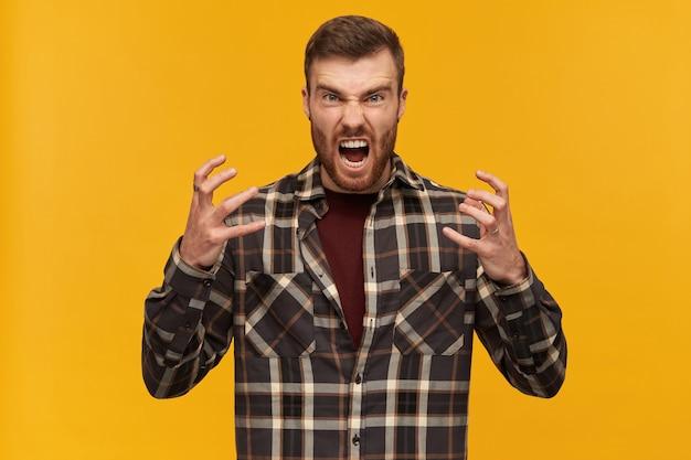 Gekke, woedende jonge, bebaarde man in een geruit overhemd houdt de handen omhoog en ziet er gek en geïrriteerd uit over de gele muur