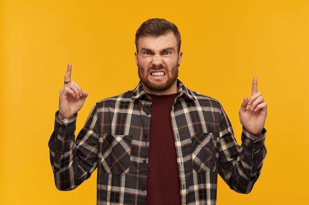 Gekke woedende jongeman in geruit overhemd met baard die met beide handen naar de hemel wijst en naar de voorkant kijkt over de gele muur