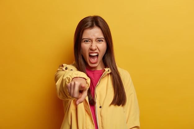 Gekke woedende vrouw die boos en geïrriteerd op je is, wijst direct met wijsvinger, geeft iemand de schuld, heeft ruzie, schreeuwt woedend, ontevreden over wat ze van voren ziet, draagt gele jas