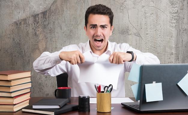 Gekke zakenman die document splitst bij het bureau.