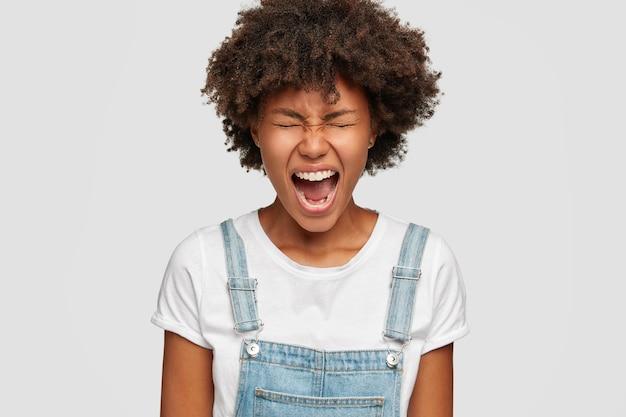 Gekke zwarte vrouw geïrriteerd door domme collega's, fronst gezicht van ongenoegen, huilt wanhopig