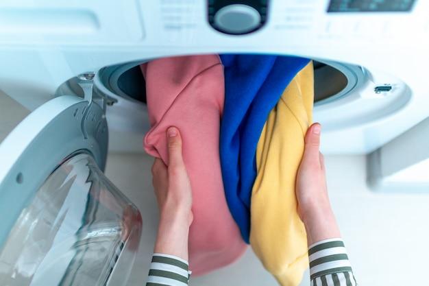 Gekleurd kleding en linnengoed in de wasmachine laden. thuis de was doen. bovenaanzicht