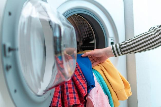 Gekleurd kleding en linnengoed in de wasmachine laden. thuis de was doen