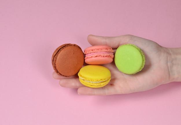Gekleurd makarons in hand close-up op een roze achtergrond