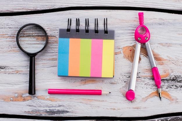 Gekleurd notitieblok met roze potlood en verdelers. schoolaccessoires op witte houten tafel.