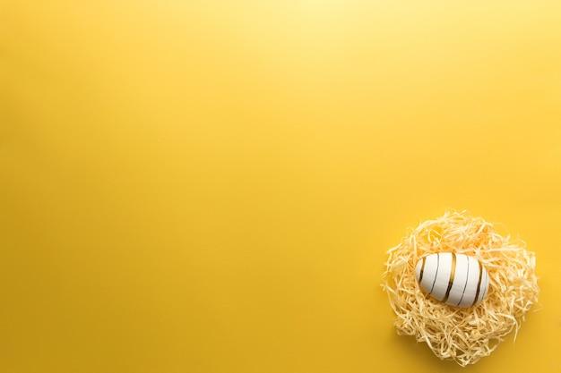 Gekleurd paasei in nest op gele achtergrond. hoge kwaliteit foto