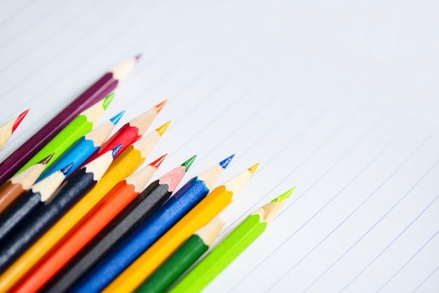 Gekleurd potlood dat op witboeknotitieboekje terug naar school en van het onderwijsconcept / kleurrijke kleurpotloden wordt geplaatst