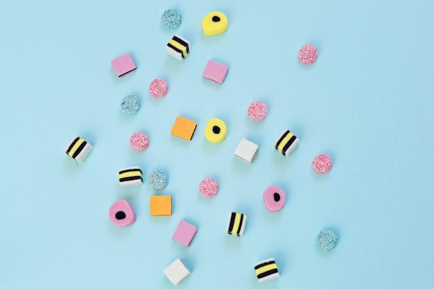 Gekleurd suikergoed verspreid op de blauwe achtergrond