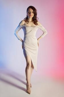 Gekleurde achtergrond, neonlichten, studio-opname. mode portret van een jonge elegante brunette vrouw.