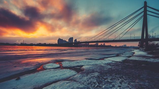 Gekleurde avondwolken drijven over half bevroren dnipro-rivier