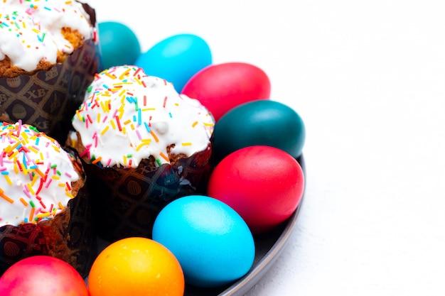 Gekleurde beschilderde eieren en pasen cake op een plaat op een wit.