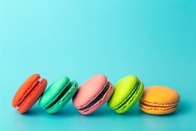 Gekleurde bitterkoekjes (macarons) cookies op een blauwe achtergrond. heldere feestelijke gebakjes, desserts en snoepjes. bakken achtergrond