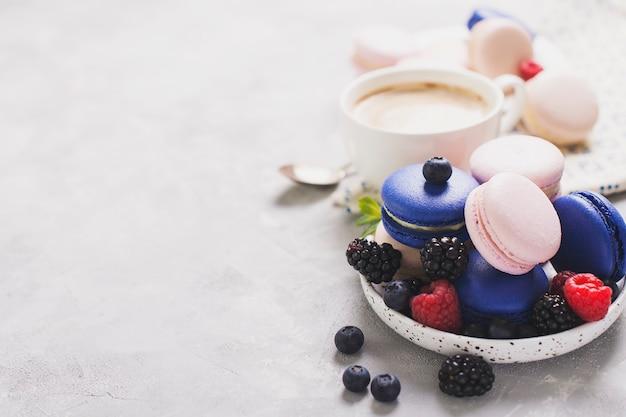 Gekleurde bitterkoekjes met kopje koffie en bessen op wit