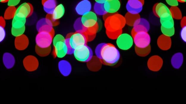 Gekleurde bokeh op een zwarte achtergrond. kleurrijke bokeh achtergrond
