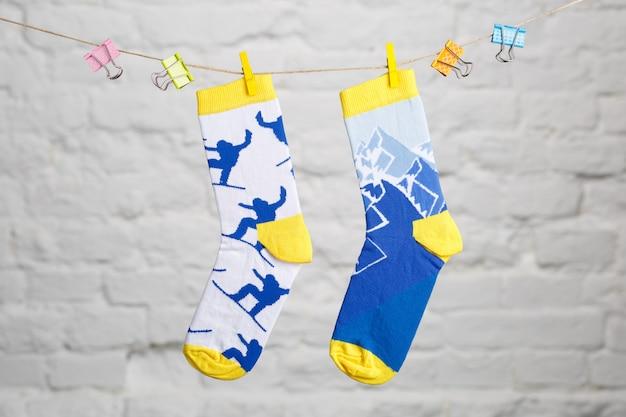 Gekleurde casual sokken opknoping op een draad en vastgebonden op een witte achtergrond.